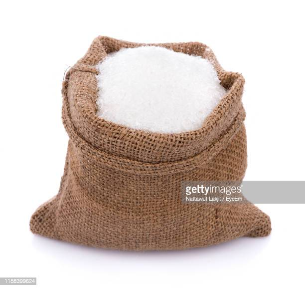 close-up of sugar in sack against white background - sucre photos et images de collection