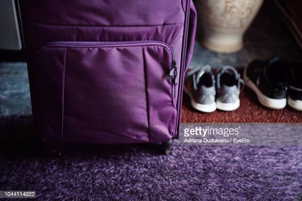 close-up of suitcase and shoes on rug - purple shoe stock pictures, royalty-free photos & images