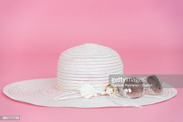 close-up of sun hat with sunglasses against pink background - サングラス 無人 ストックフォトと画像