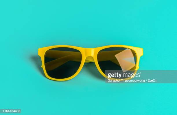close-up of sunglasses against blue background - sunglasses stock pictures, royalty-free photos & images