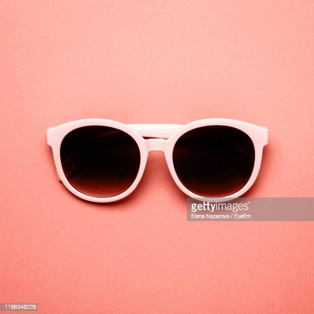 close-up of sunglasses against coral background - sunglasses stock pictures, royalty-free photos & images