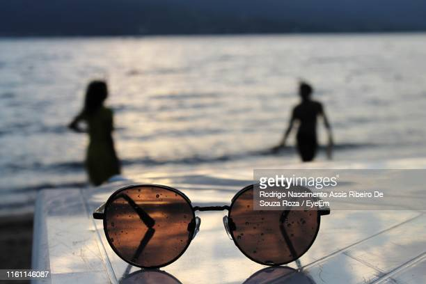 close-up of sunglasses against silhouette people at beach - assis ストックフォトと画像