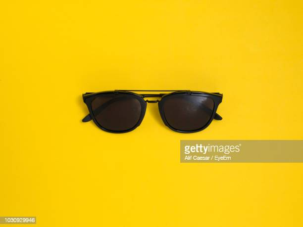 close-up of sunglasses against yellow background - sunglasses stock pictures, royalty-free photos & images
