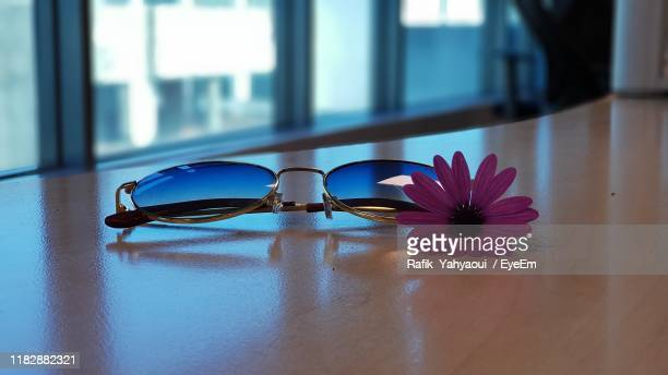 close-up of sunglasses and flower on table at home - サングラス 無人 ストックフォトと画像