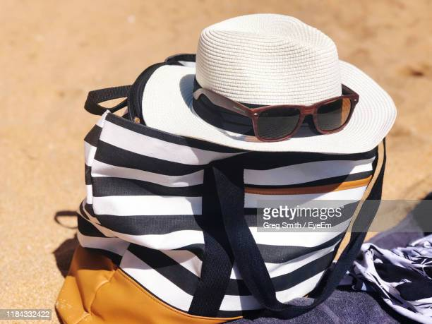 close-up of sunglasses and hat on bag at beach - tote bag stock pictures, royalty-free photos & images