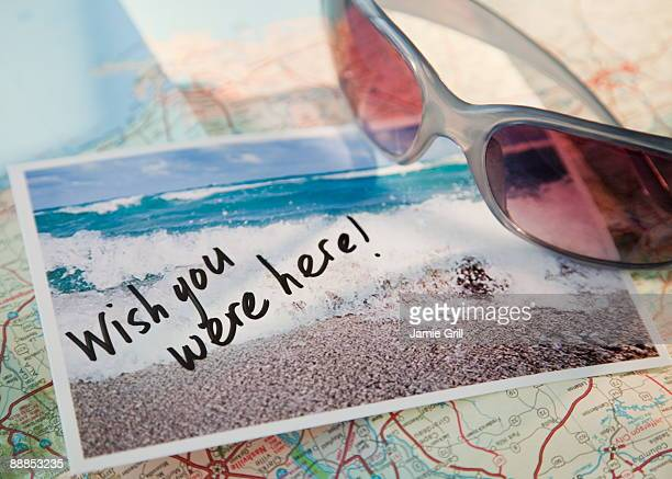close-up of sunglasses and postcard on map - postcard stock pictures, royalty-free photos & images