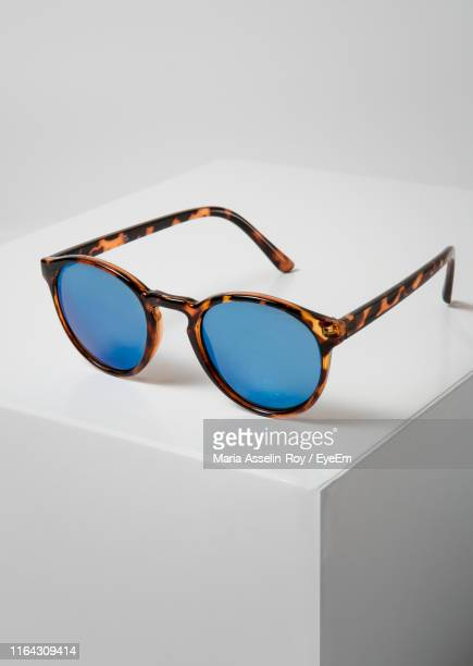 close-up of sunglasses on box against white background - めがね類 ストックフォトと画像