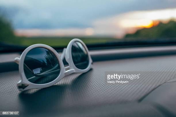 Close-up of sunglasses on car dashboard against windshield