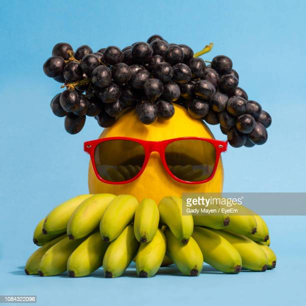 Close-Up Of Sunglasses On Fruits Over Blue Background