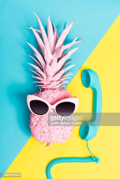 close-up of sunglasses on pineapple with telephone receiver on colored background - two tone color stock pictures, royalty-free photos & images