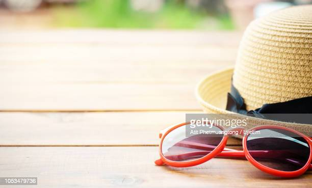 close-up of sunglasses on table - straw hat stock pictures, royalty-free photos & images