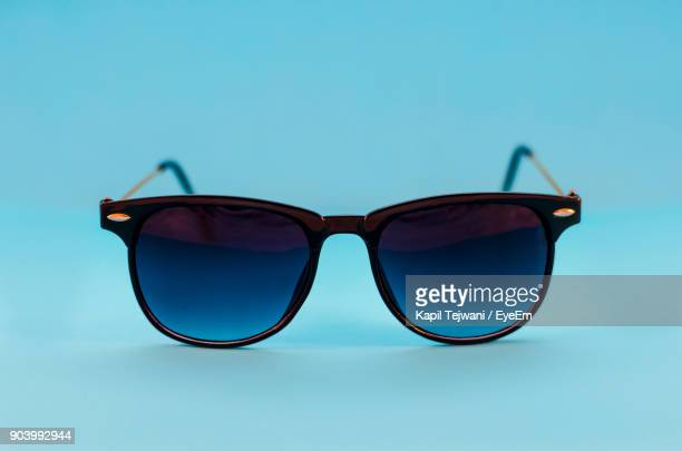 close-up of sunglasses over blue background - sunglasses stock pictures, royalty-free photos & images
