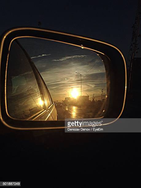 Close-up of sunset reflecting on side-view mirror