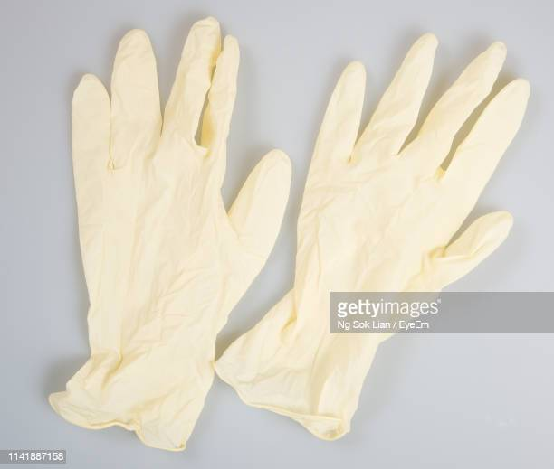 close-up of surgical gloves on gray background - surgical glove stock pictures, royalty-free photos & images