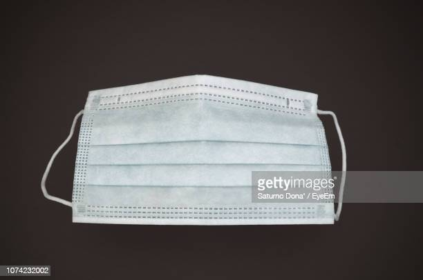 close-up of surgical mask over black background - cloth face mask stock pictures, royalty-free photos & images