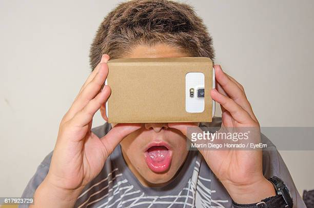 Close-Up Of Surprised Boy Looking In Smart Phone Through Cardboard Virtual Reality Simulator