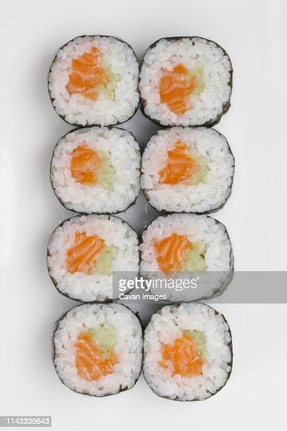 close-up of sushi rolls arranged on white background - maki sushi stock pictures, royalty-free photos & images