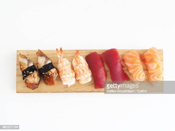 Close-Up Of Sushi Served On Cutting Board Over White Background