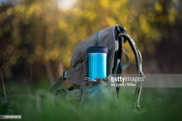 close-up of sustainable, reusable bottle in backpack on field, inwad, poland - nature stock pictures, royalty-free photos & images