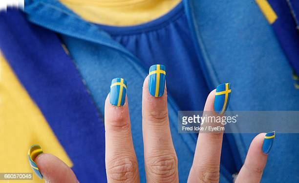 Close-Up Of Swedish Flag Represented On Woman Nails