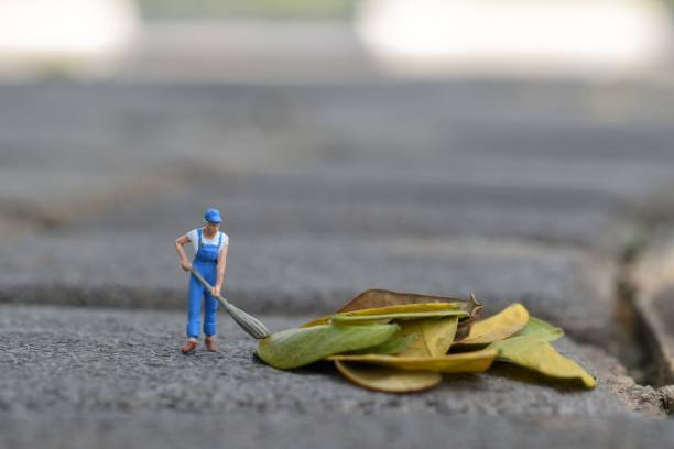 Close-Up Of Sweeper Figurine With Dry Leaves On Footpath