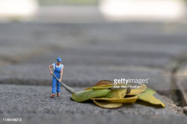 close-up of sweeper figurine with dry leaves on footpath - rappresentazione umana foto e immagini stock