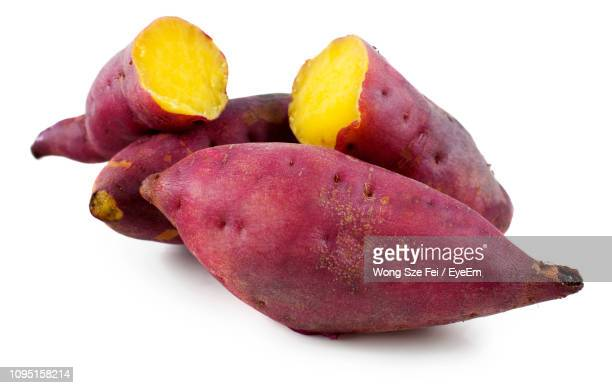 close-up of sweet potatoes against white background - sweet potato stock pictures, royalty-free photos & images