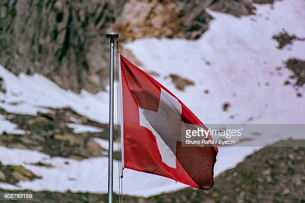 Close-Up Of Swiss Flag Against Mountains During Winter