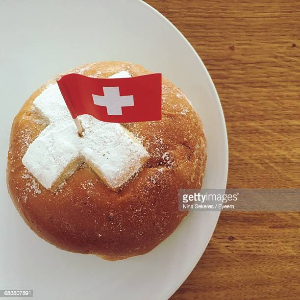 close-up of swiss flag stuck in bread on plate - drapeau suisse photos et images de collection