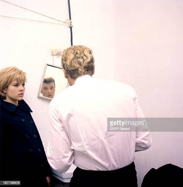 CloseUp Of Sylvie Vartan And Johnny Hallyday En 1963 dans les coulisses lors d'un concert le chanteur Johnny HALLYDAY de dos se regardant dans un...