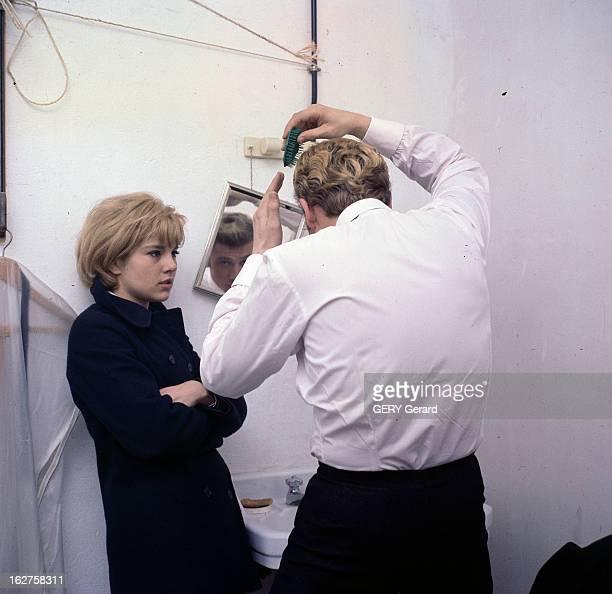 CloseUp Of Sylvie Vartan And Johnny Hallyday En 1963 dans les coulisses lors d'un concert le chanteur Johnny HALLYDAY de dos se coiffant aux côtés de...