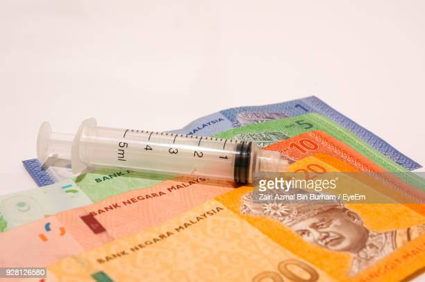 close-up of syringe on paper currency over white background - malaysian ringgit stock photos and pictures