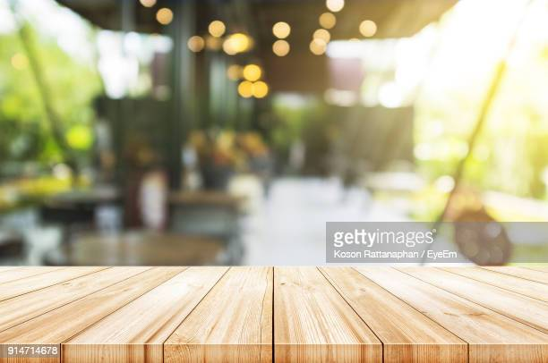 close-up of table against illuminated lights - wood table stock photos and pictures