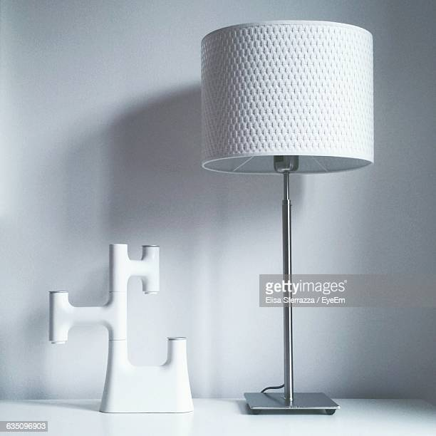 Close-Up Of Table Lamp Against The Wall