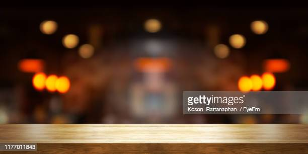close-up of table with illuminated lights in background - focus on foreground stock pictures, royalty-free photos & images