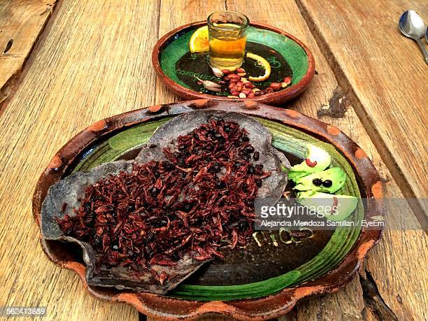 Close-Up Of Taco With Fried Insects In Plate And Drink On Table