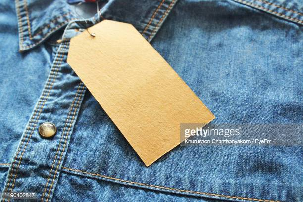 close-up of tag on shirt - label stock pictures, royalty-free photos & images