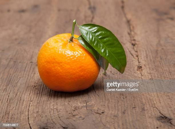 close-up of tangerine on wooden table - ミカン ストックフォトと画像