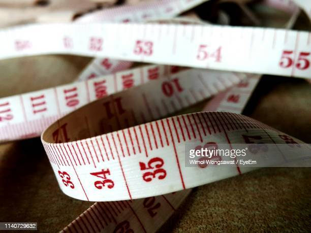 close-up of tape measure on table - wimol wongsawat stock photos and pictures