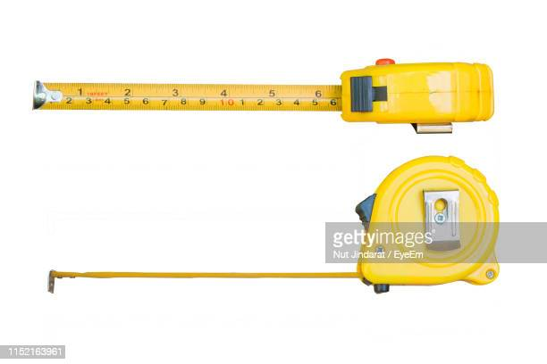 close-up of tape measures against white background - tape measure stock pictures, royalty-free photos & images