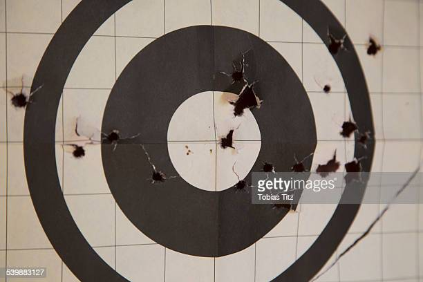 close-up of target with bullet holes - bullet hole stock pictures, royalty-free photos & images