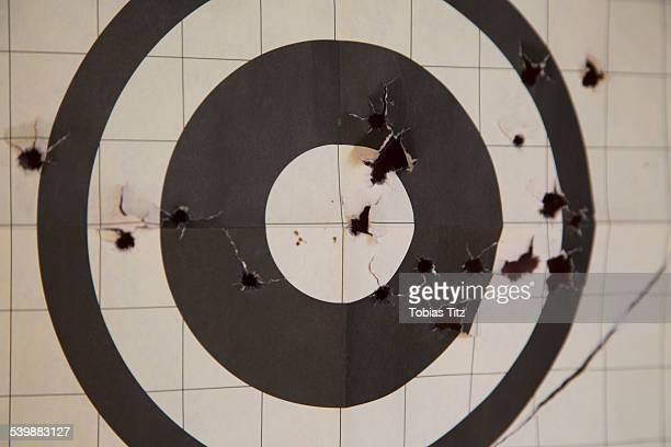 close-up of target with bullet holes - agujero de bala fotografías e imágenes de stock