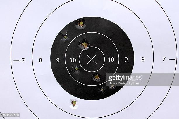 close-up of target with bullet holes - sportschießen stock-fotos und bilder