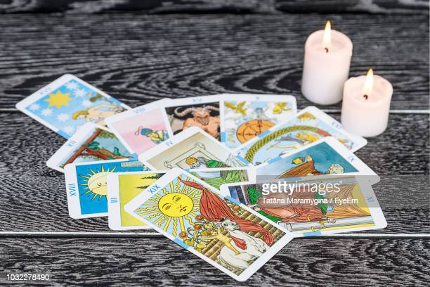 Close-Up Of Tarot Cards With Candles On Table