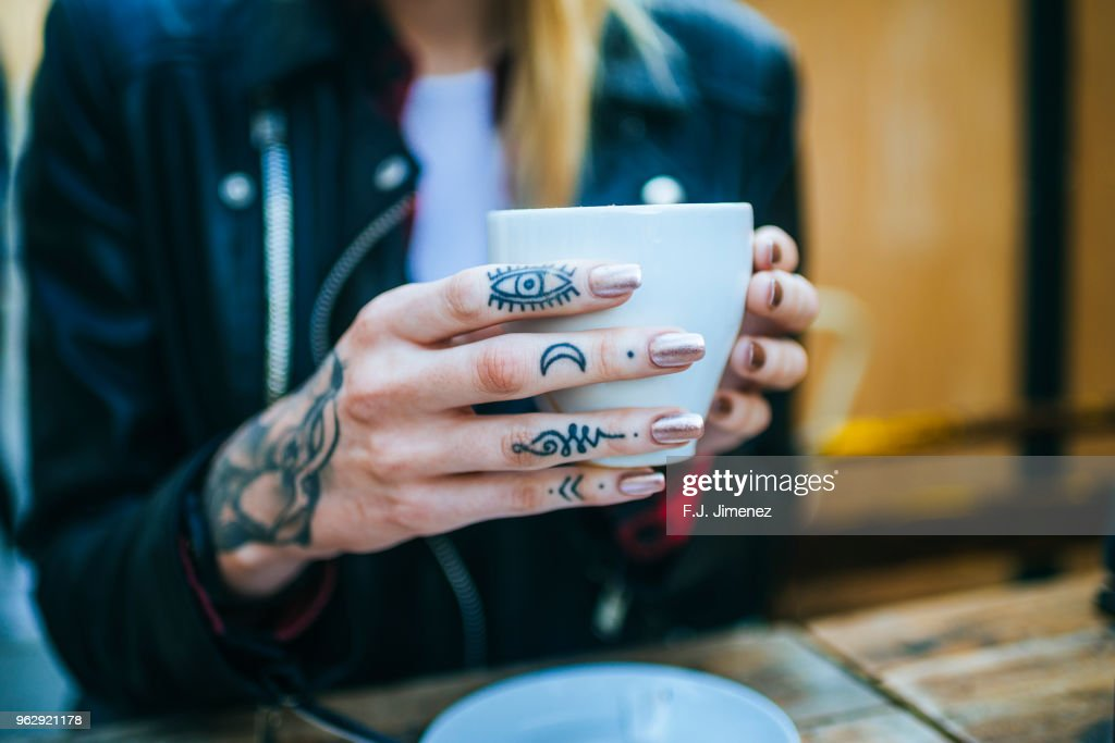 51cee8088 Closeup Of Tattooed Womans Hand With Coffee Stock Photo - Getty Images