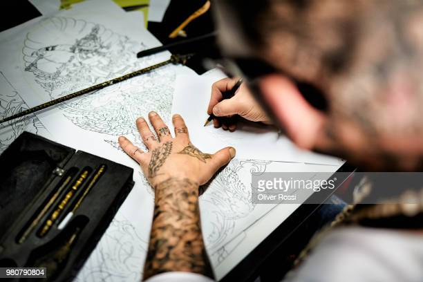 close-up of tattooist working on draft at desk in his studio - sketch stock pictures, royalty-free photos & images