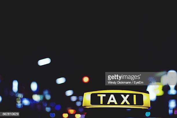 Close-Up Of Taxi Sign Against Illuminated Lights At Night