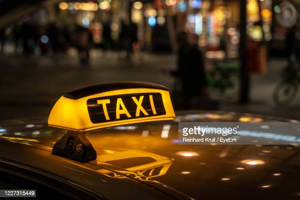 close-up of taxi sign on street in city at night - イエローキャブ ストックフォトと画像