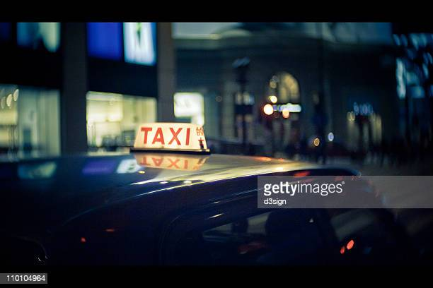 Close-up of taxi sign with reflection at night