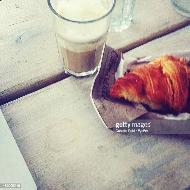 close-up of tea and croissant on wooden table - danielle reid stock pictures, royalty-free photos & images